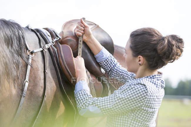 Mulher apertando sela de cavalo para passeios a cavalo — Fotografia de Stock