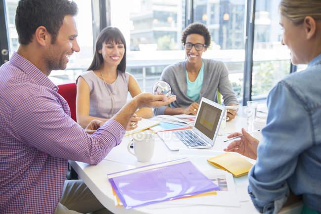 Uomini d'affari che esaminano palla in ufficio — Foto stock