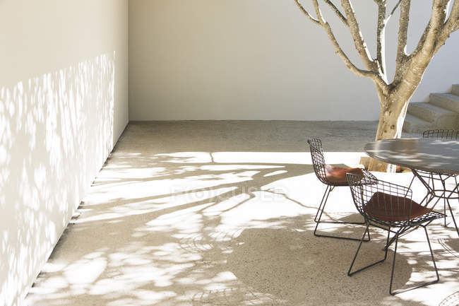Table and chairs casting shadows in courtyard — Stock Photo