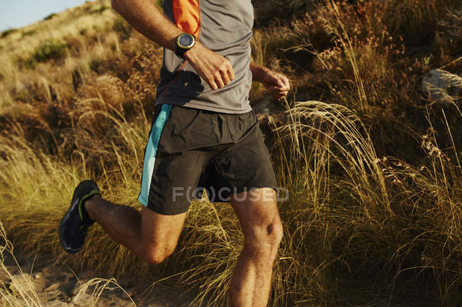 Man running on trail through tall grass — Stockfoto