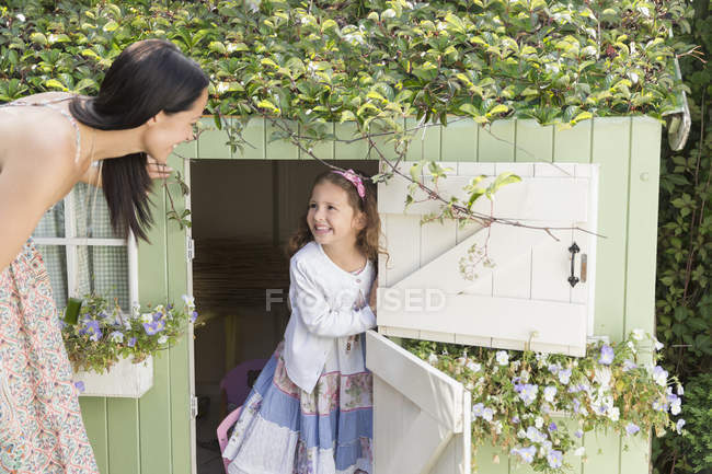 Mother and daughter at playhouse in garden — Stock Photo