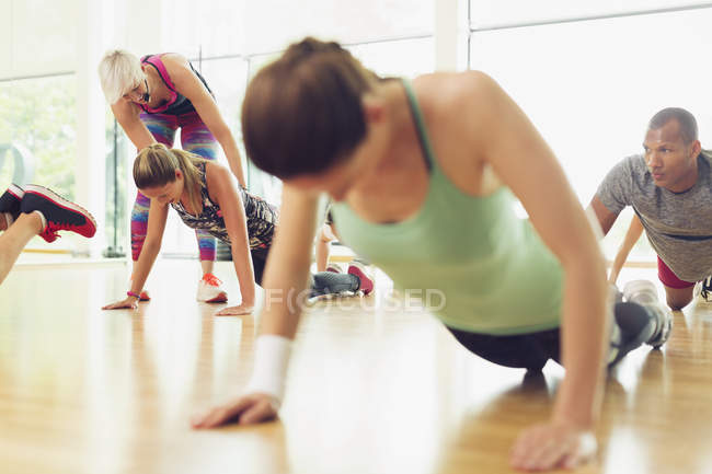 Fitness instructor guiding woman in exercise class — Stock Photo