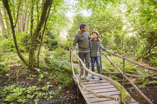 Батько і син перетину місток в лісі — стокове фото