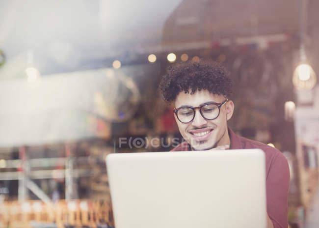 Uomo sorridente con i capelli neri ricci utilizzando il computer portatile alla finestra del caffè — Foto stock