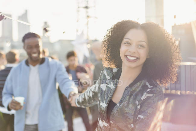 Smiling young couple holding hands at rooftop party — Stockfoto