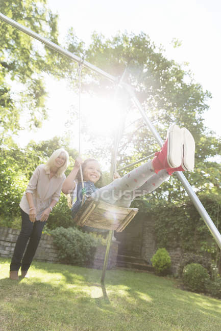 Grandmother pushing carefree granddaughter on swing in backyard — Stock Photo