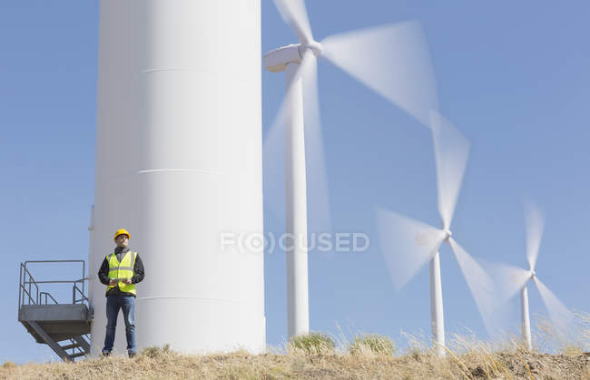 Worker by wind turbines in rural landscape — Stock Photo