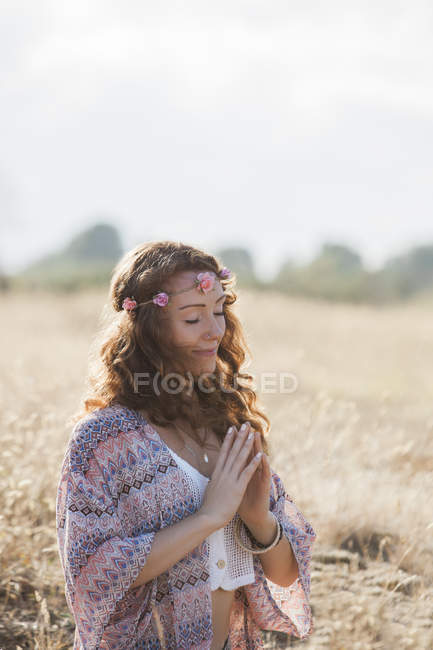 Serene boho woman meditating with hands at heart center in sunny rural field — Stock Photo