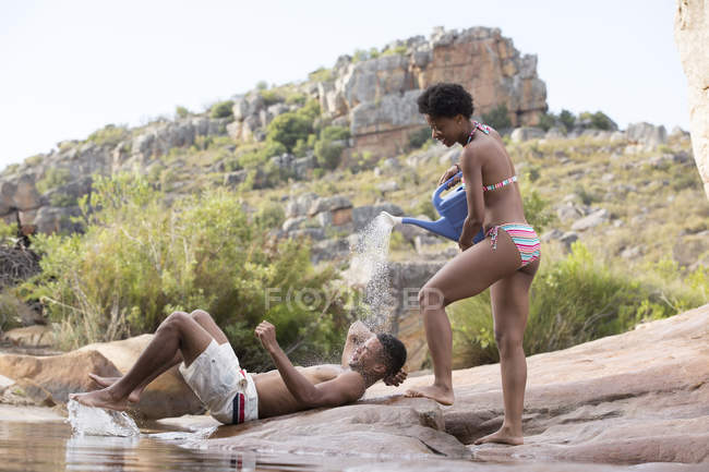 Woman splashing water on boyfriend at lakeside — Stock Photo