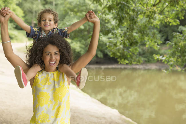 Portrait playful mother carrying son on shoulders near pond — Stock Photo