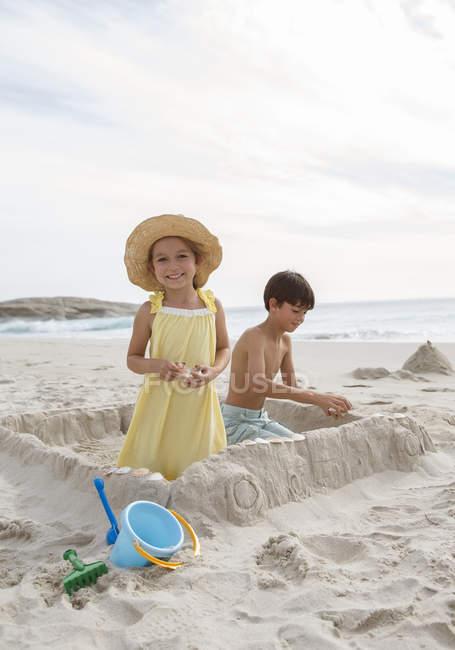 Crianças construindo castelo de areia na praia — Fotografia de Stock