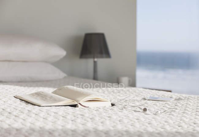 Livre et verres au lit dans une chambre moderne avec vue sur l'océan — Photo de stock