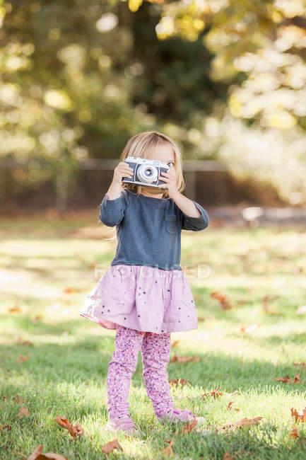 Ragazza bambino utilizzando fotocamera retrò nel parco autunnale — Foto stock