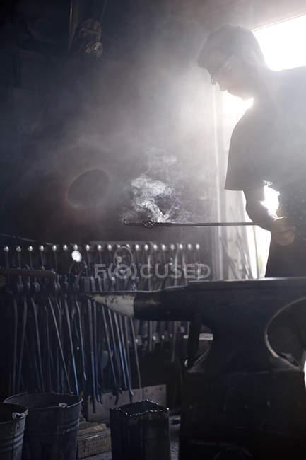 Schmied mit dampfenden Schmiedeeisen über Amboss Schmiede — Stockfoto