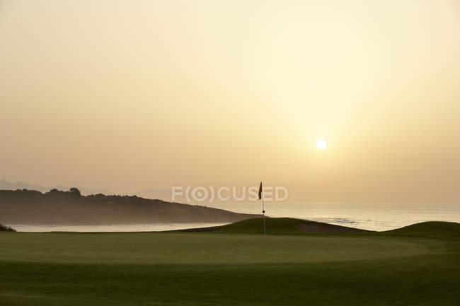 Живописный вид на закат над океаном и поле для гольфа — стоковое фото