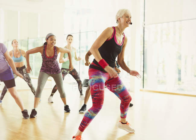 Energetic fitness instructor leading aerobics class — Stockfoto