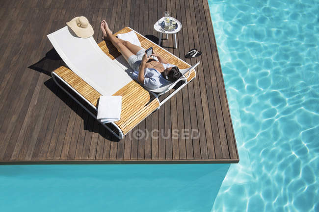 Man relaxing on lounge chair at poolside with tablet — Stock Photo