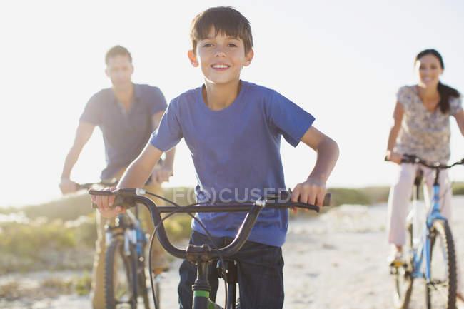 Сім'ї на велосипедах на сонячному пляжі — стокове фото