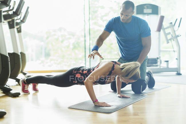 Personal trainer guiding woman doing push-ups at gym — Stock Photo