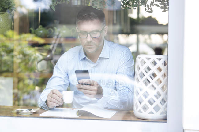 Man using smartphone while sitting at cafe table — Stockfoto
