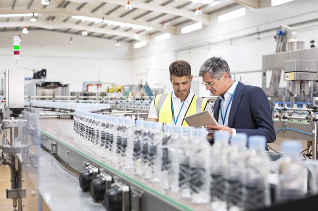 Supervisor and manager watching plastic bottles on conveyor belt — Stock Photo
