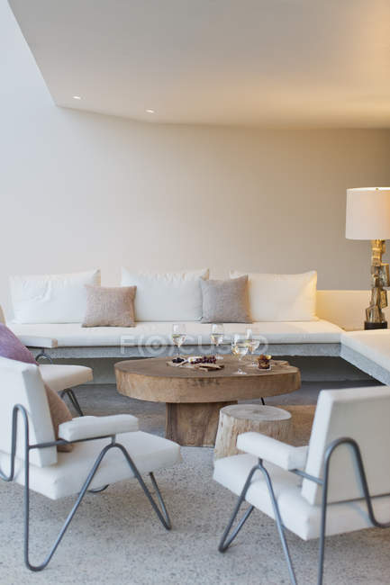 Фрукты, сыр и вино на кофейном столике в современной гостиной — стоковое фото