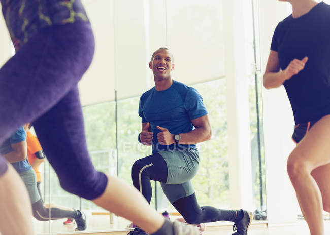 Smiling man lunging in exercise class — Stock Photo