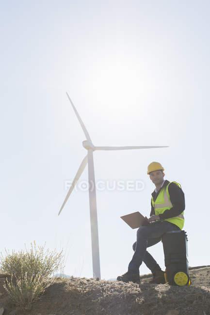 Worker using laptop by wind turbine in rural landscape — Stock Photo