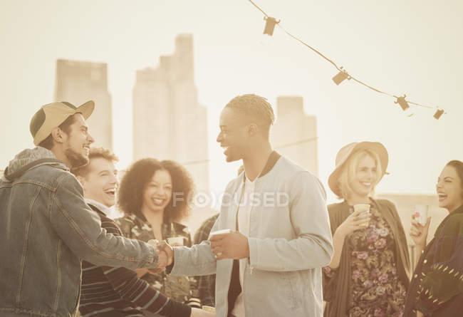 Junge Erwachsene Freunde Handshaking auf Party auf dem Dach — Stockfoto