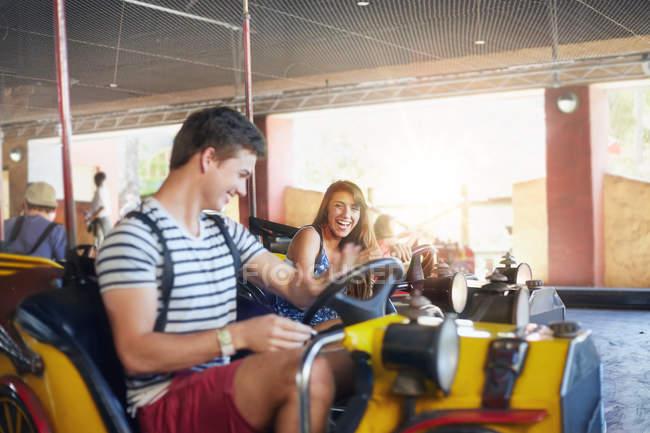 Young couple riding bumper cars at amusement park — Stock Photo