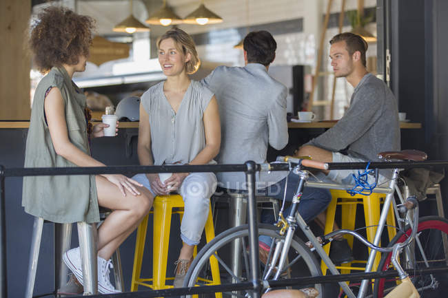 Friends hanging out talking and drinking coffee on cafe patio — Stock Photo