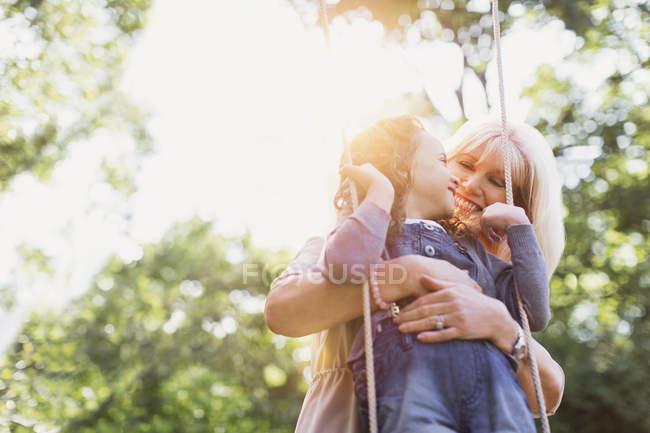 Grandmother hugging granddaughter on swing — Stock Photo