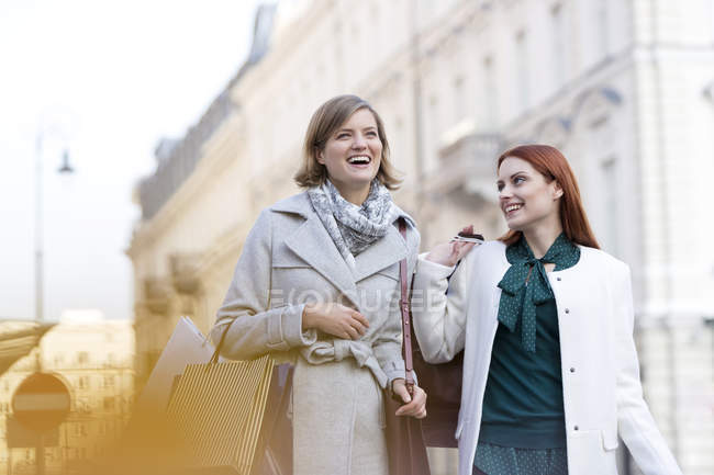 Donne sorridenti che trasportano borse della spesa in città — Foto stock