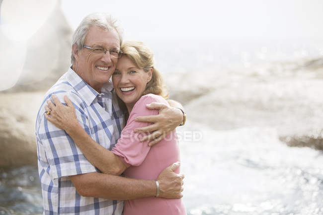 Older couple hugging on beach — Stock Photo