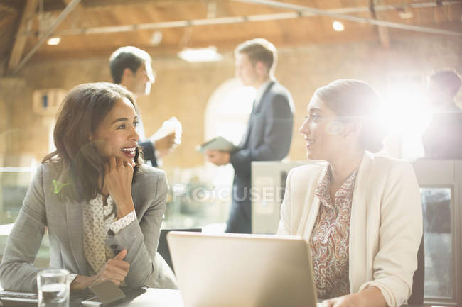 Businesswomen talking and working at laptop in office — Stock Photo