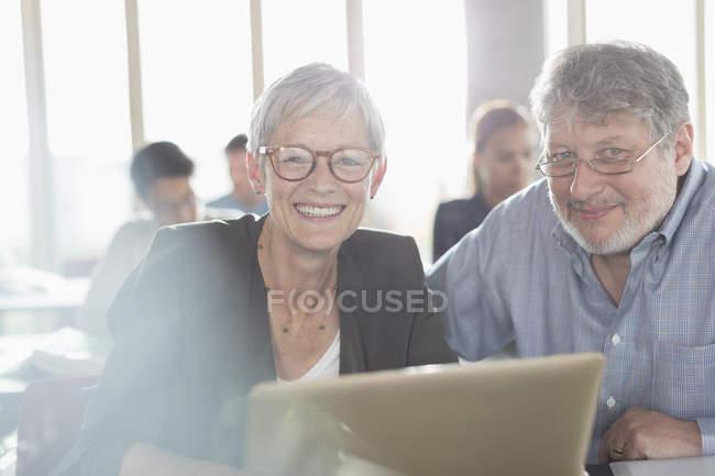 Portrait femme âgée confiante à l'ordinateur portable dans la salle de classe de l'éducation des adultes — Photo de stock