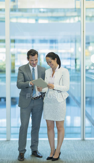 Businessman and businesswoman using digital tablet in office — Stock Photo