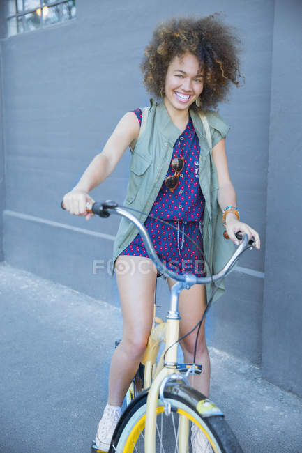Portrait smiling woman with afro on bicycle — Stock Photo