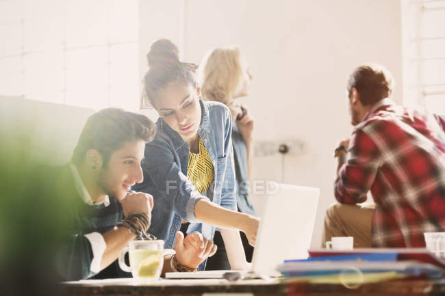 Creative young business people working at laptop in office — Stock Photo