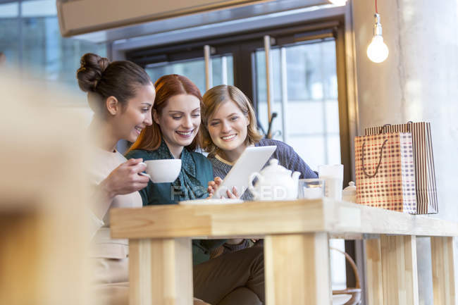 Smiling women drinking tea and sharing digital tablet at cafe counter — Stock Photo