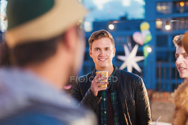 Young adult friends talking and drinking at nighttime rooftop party — Stockfoto