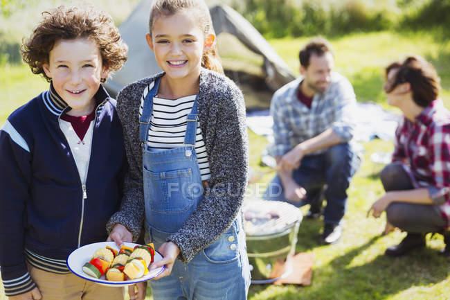 Портрет улыбающиеся брат и сестра с овощными шампурами в кемпинге — стоковое фото