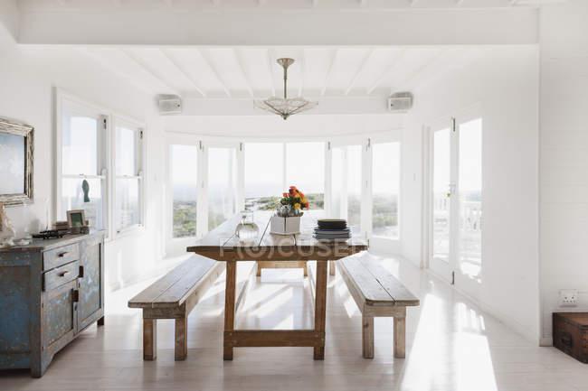 Деревянный стол и скамейки в солнечном столовом зале — стоковое фото
