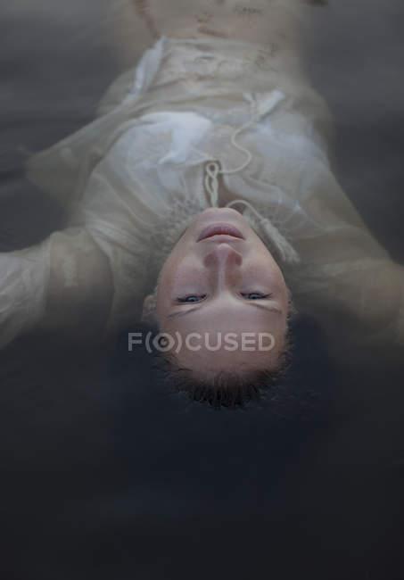 Mulher Serena flutuando no lago — Fotografia de Stock