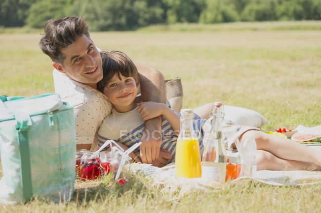 Porträt liebevoller Vater und Sohn auf der Picknickdecke im sonnigen Bereich entspannend — Stockfoto