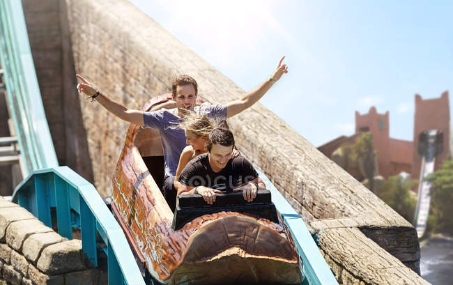 Young man cheering on log amusement park ride — Stock Photo