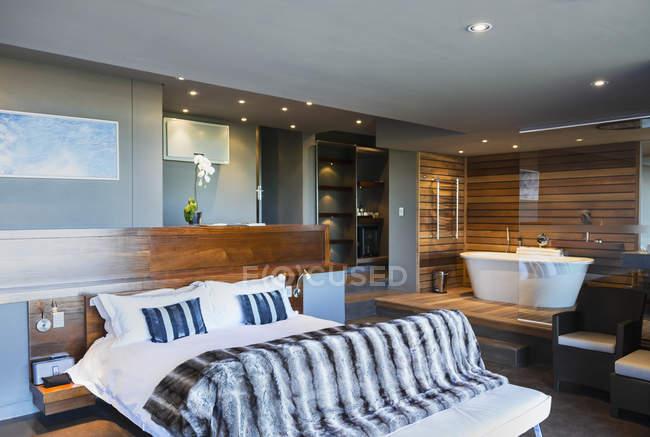 Letto e vasca da bagno nella camera da letto moderna master ...