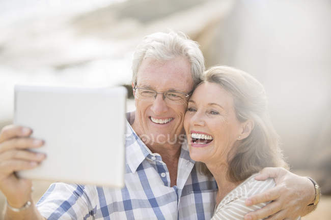 Older couple taking pictures with digital tablet — Stock Photo