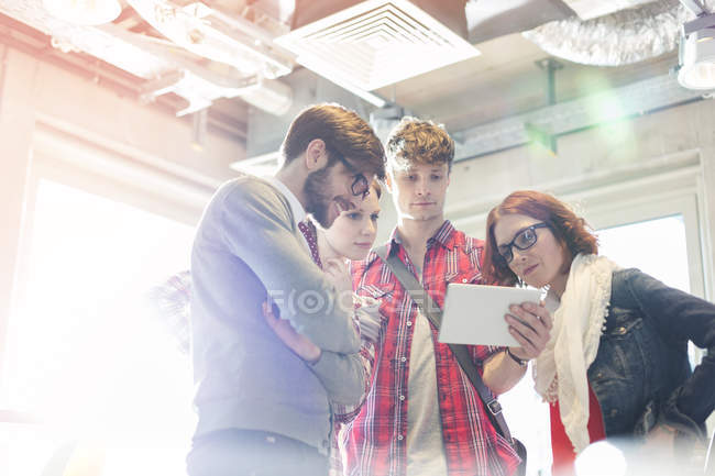 Creative business people sharing digital tablet in sunny office — Stock Photo