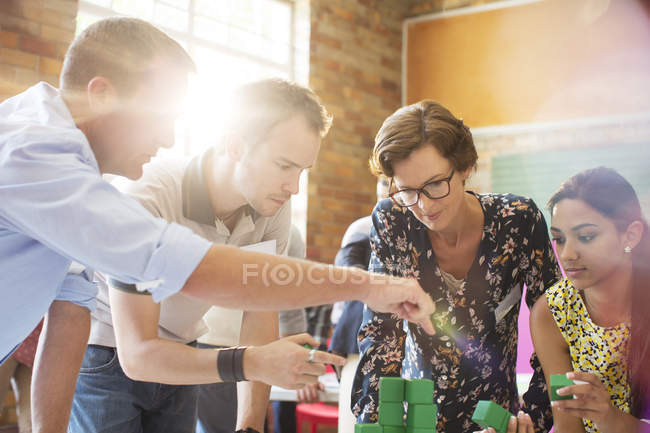 Focused business people stacking green blocks — Stock Photo